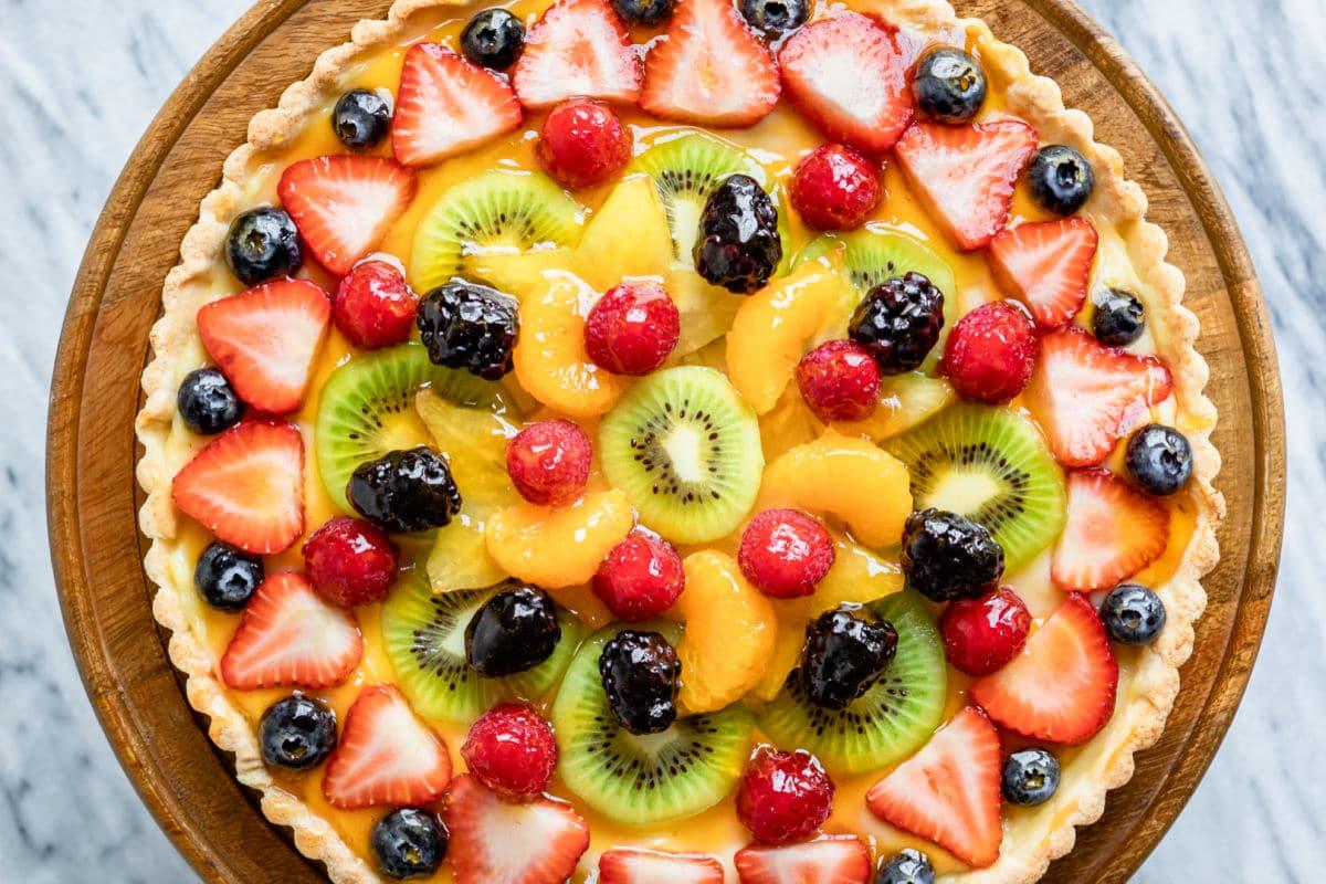 An overhead shot of fresh fruit tart on a wooden stand.