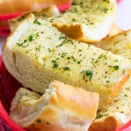 Garlic bread in a plastic red basket.