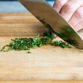 Someone chiffonading basil on a cutting board.