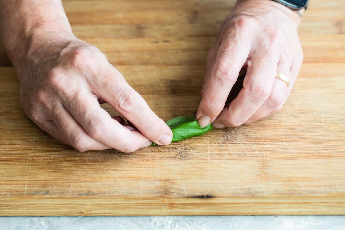 Someone rolling basil on a wooden cutting board.