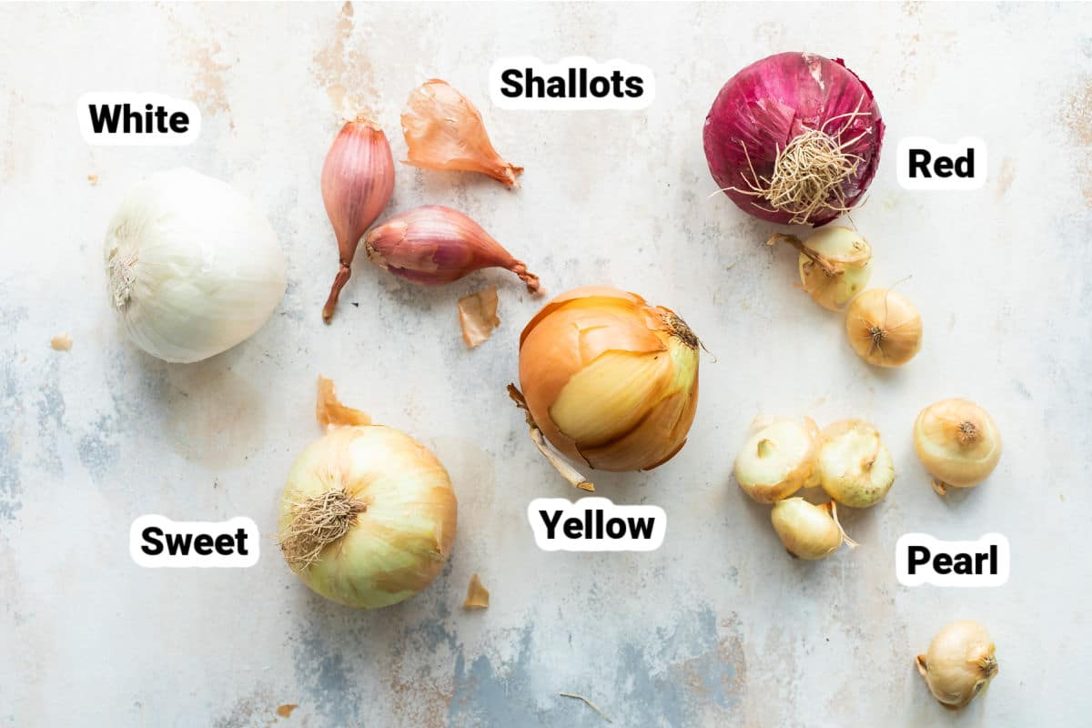 Different types of onions labeled on a board.