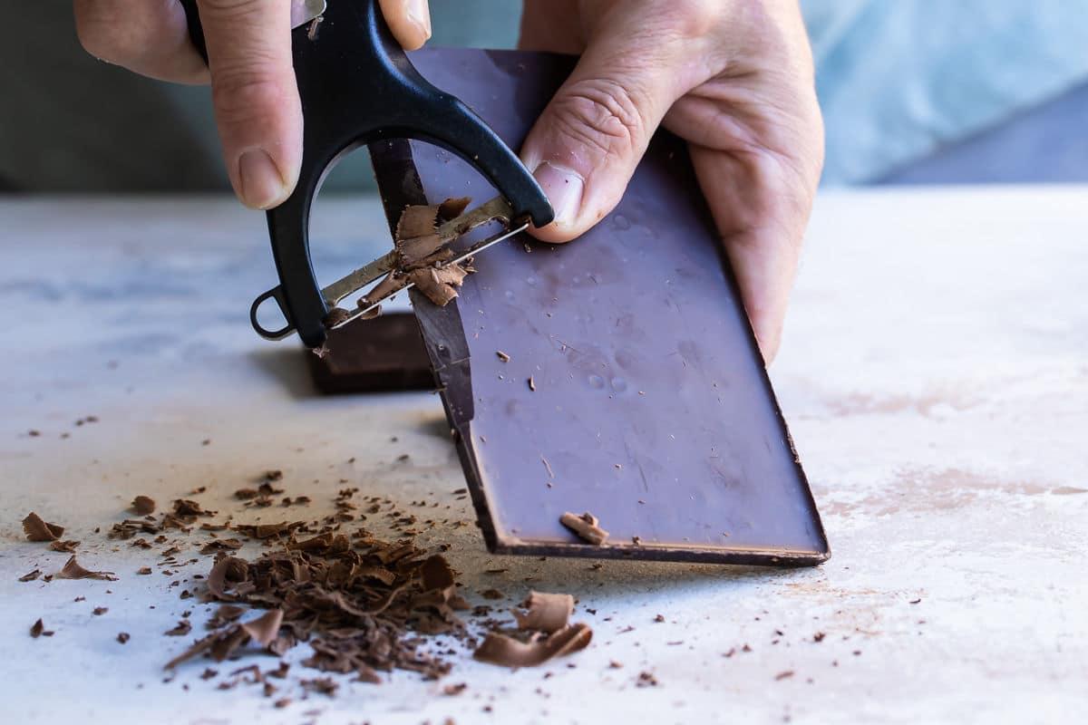 Shaving chocolate curls off a bar of chocolate.