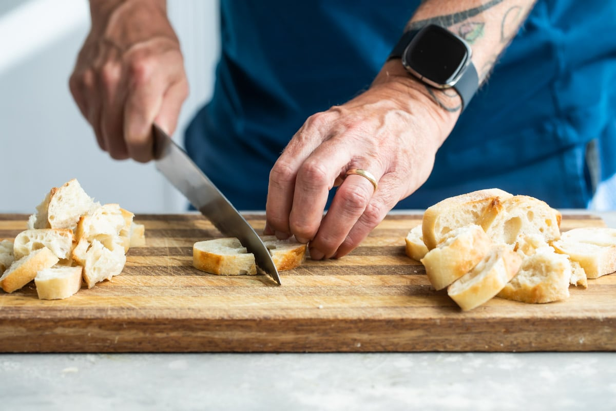 Someone cutting a slice of bread on a wooden cutting board.