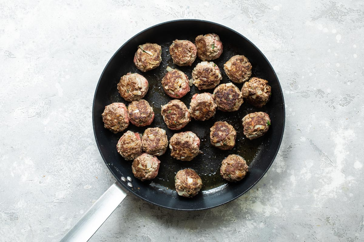Meatballs being cooked in a black skillet.
