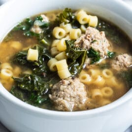 Italian wedding soup in a white bowl.