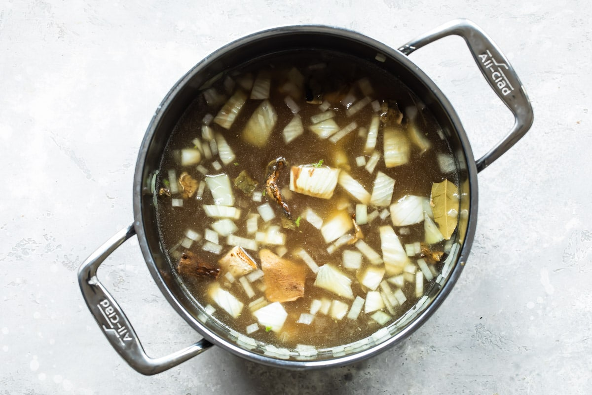 A stock pot with vegetables and broth in it.