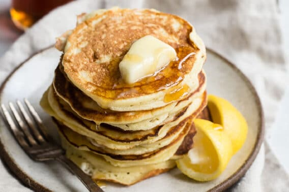 A stack of lemon ricotta pancakes on a plate.