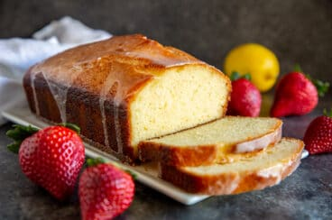 Lemon Yogurt Cake with some slices cut off the loaf, surrounded by fresh strawberries and a lemon.