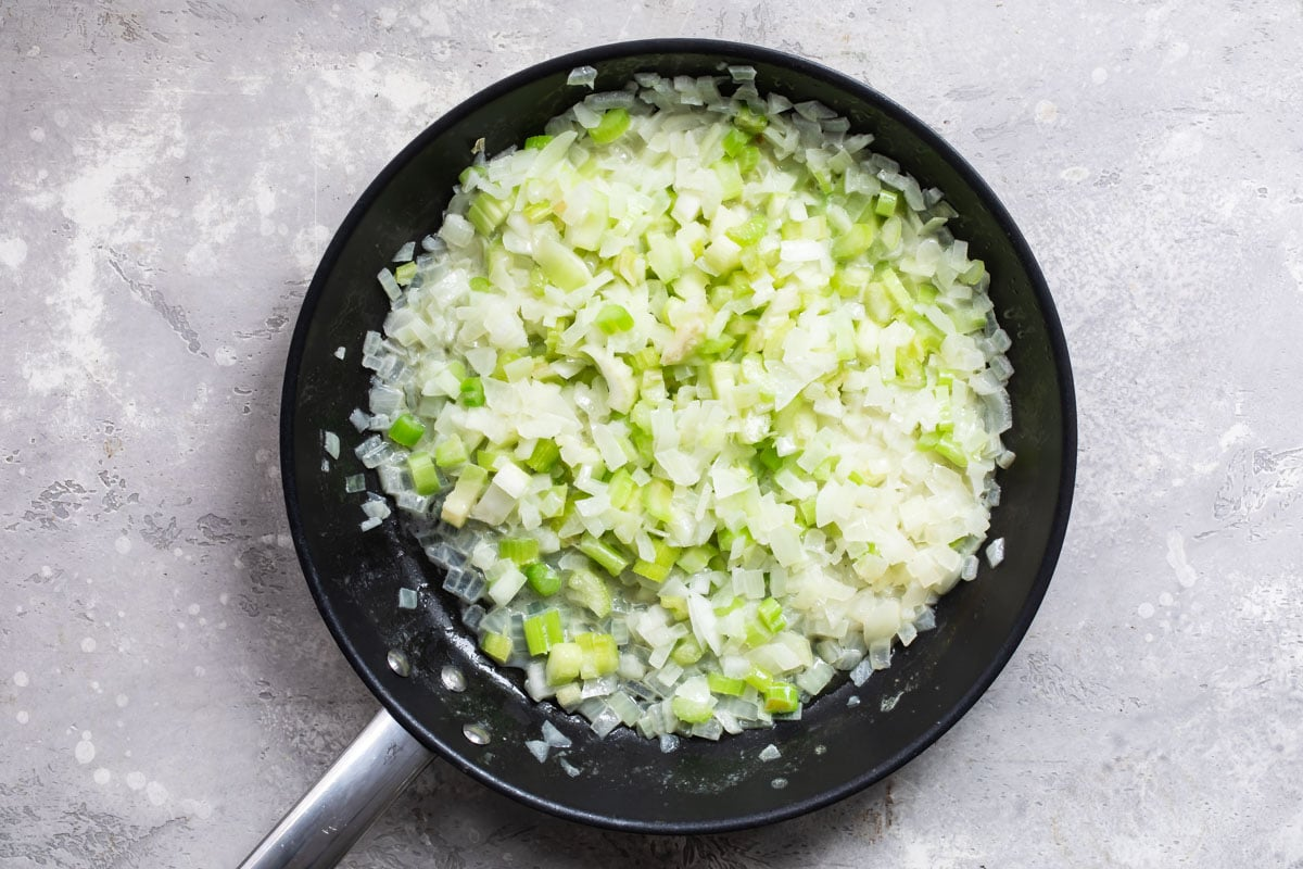 Onions and celery cooking in a skillet.