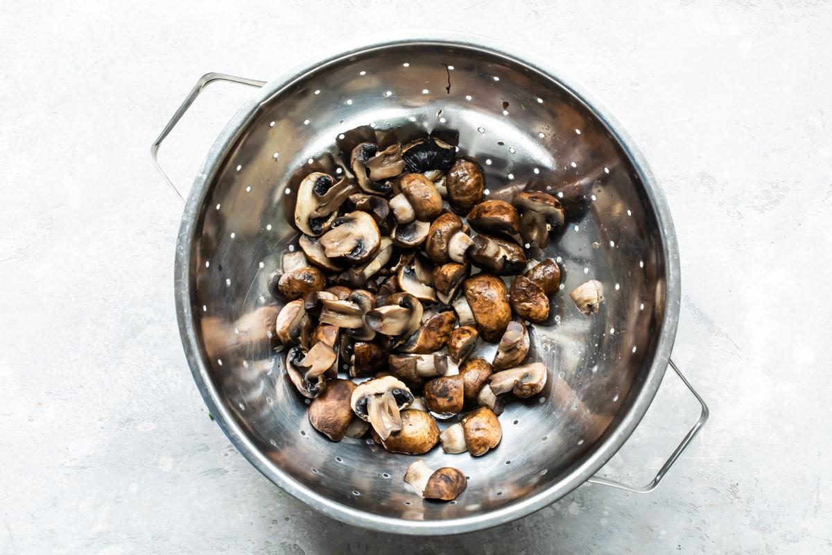 Mushrooms in a silver colander.