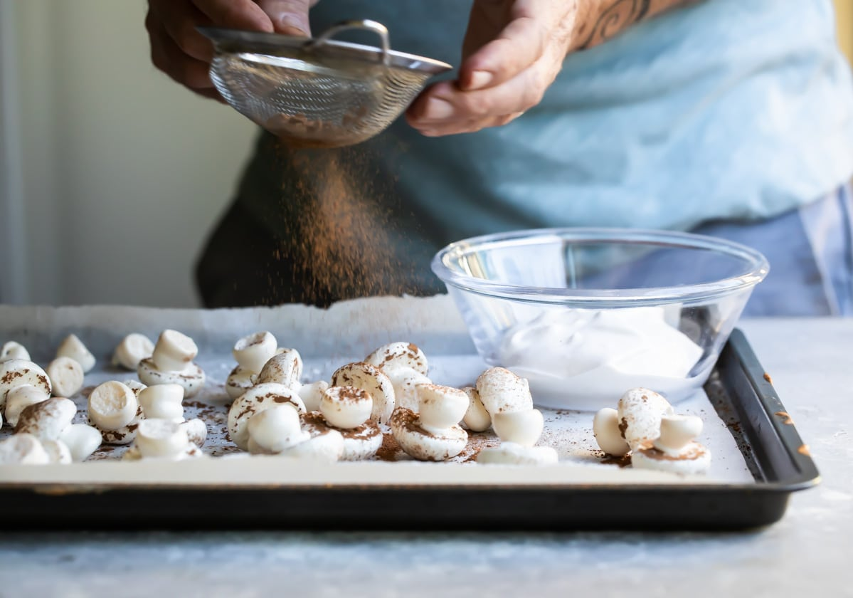 Dusting meringue mushrooms with cocoa powder.