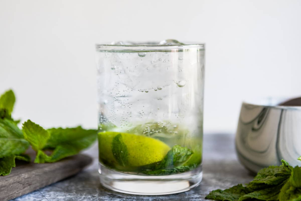A mojito cocktail in a low-ball glass.