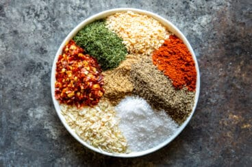 A plate with Montreal Steak Seasoning ingredients before mixing.