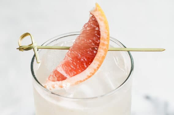 A collins glass with a Paloma cocktail in it, garnished with a grapefruit wedge.