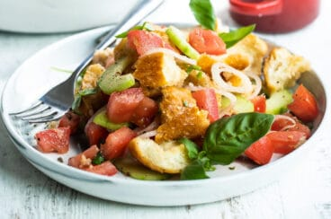 Two plates with Panzanella salad.