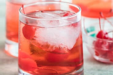Shirley temples in three clear glasses with a clear bowl filled with cherries.