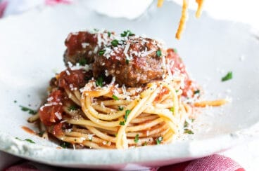 Someone rolling spaghetti noodles on a fork over a plate of spaghetti and meatballs.