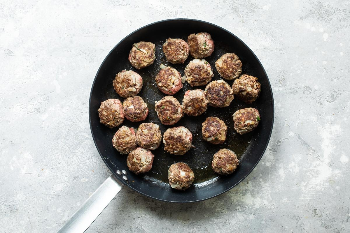 Meatballs being browned in a skillet.