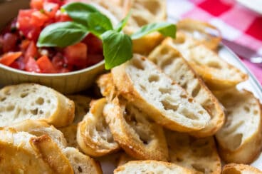 Toasted baguettes on a white platter with bruschetta.