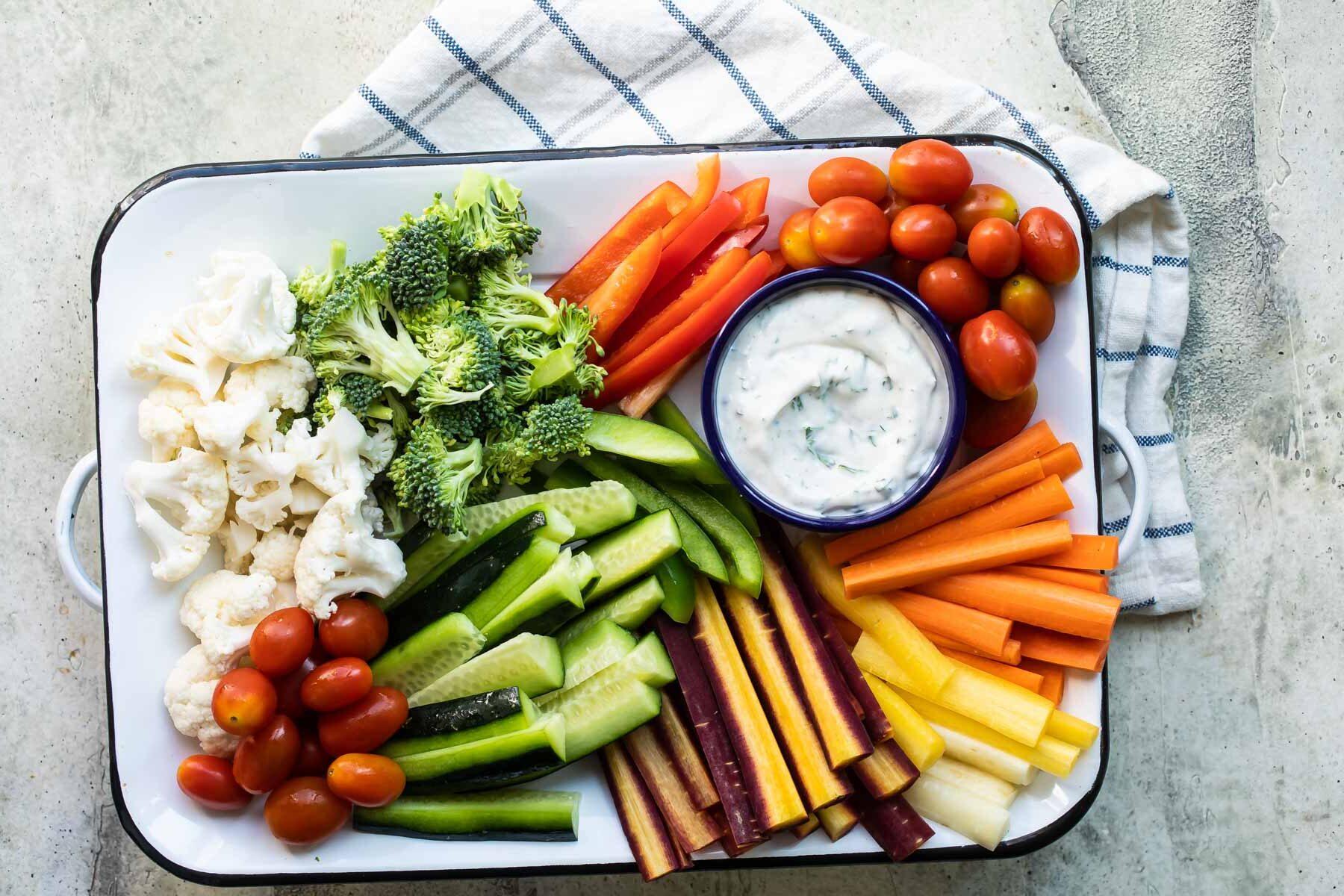 Veggies and veggie dip on a white rectangular platter.