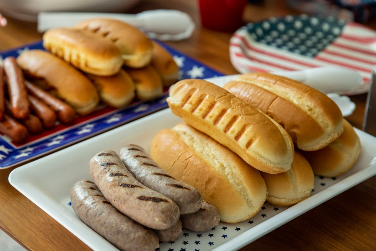 A table of 4th of July Cookout food such as brats, hot dogs, pasta salad, cookies, and drinks.