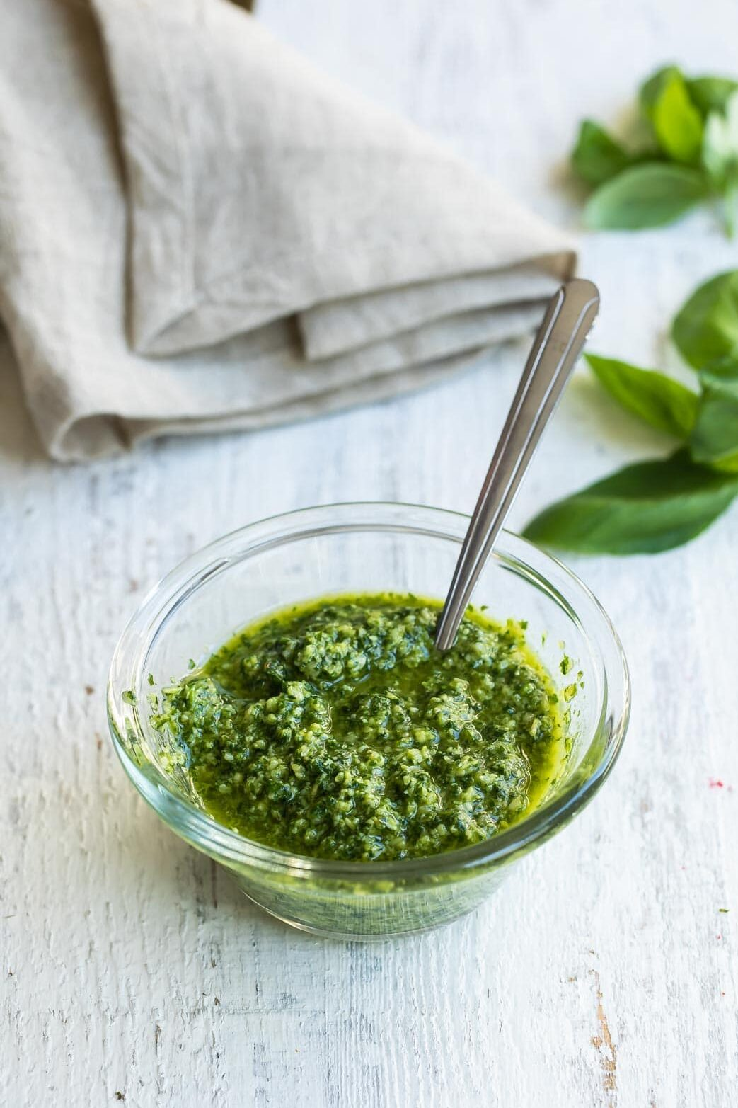 Basil pesto in a clear bowl with a spoon.