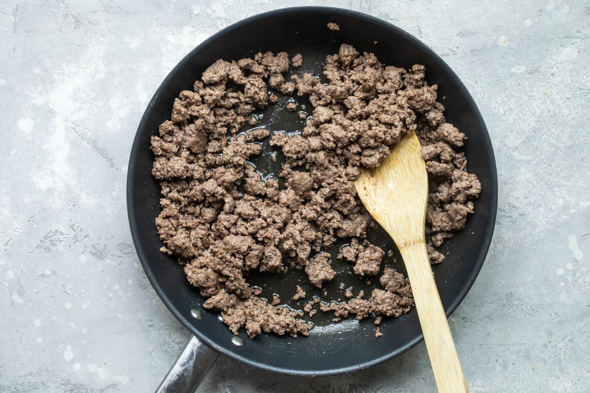 A skillet with cooked hamburger.