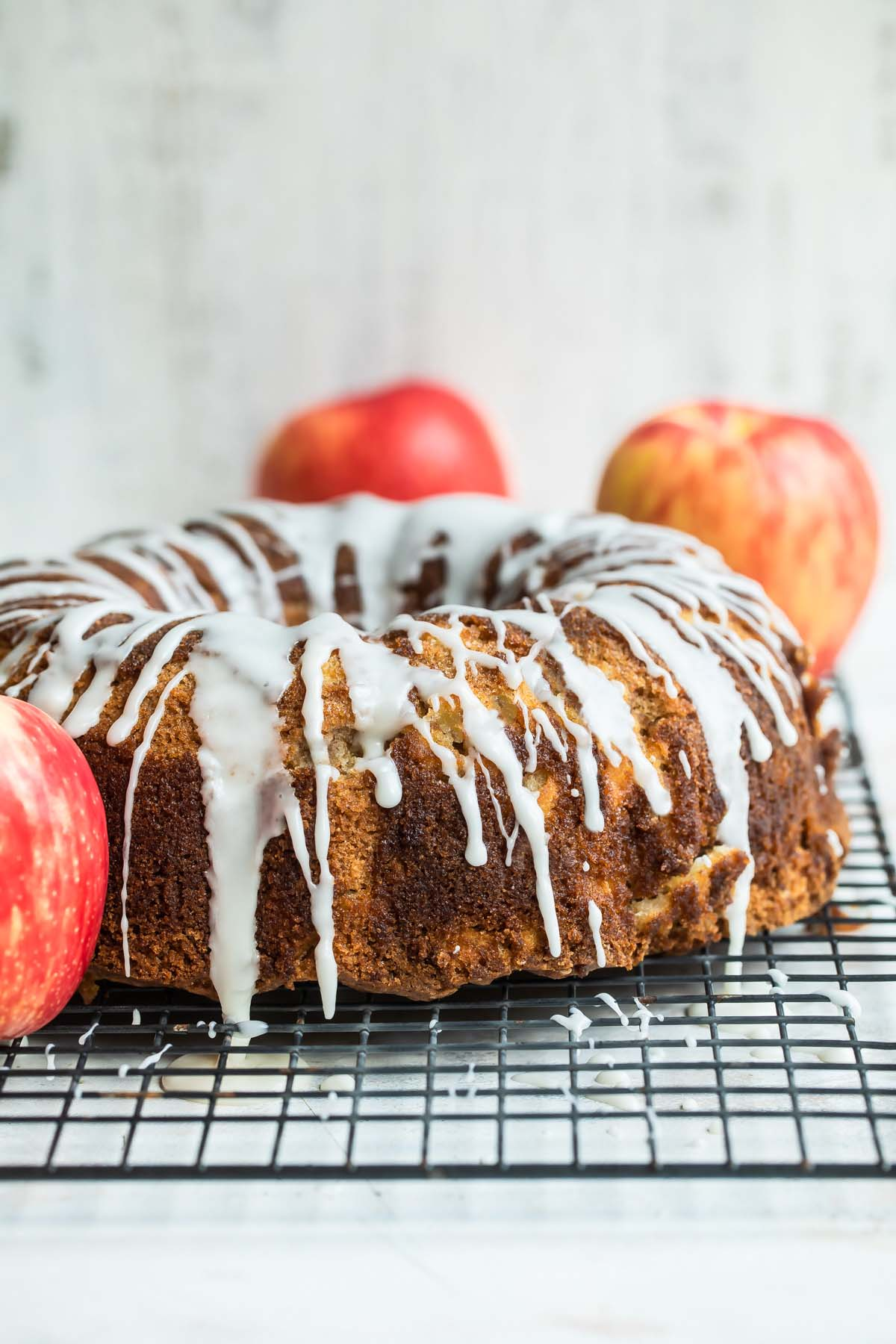 Cinnamon Apple Cake on a cooling rack surrounded by apples.