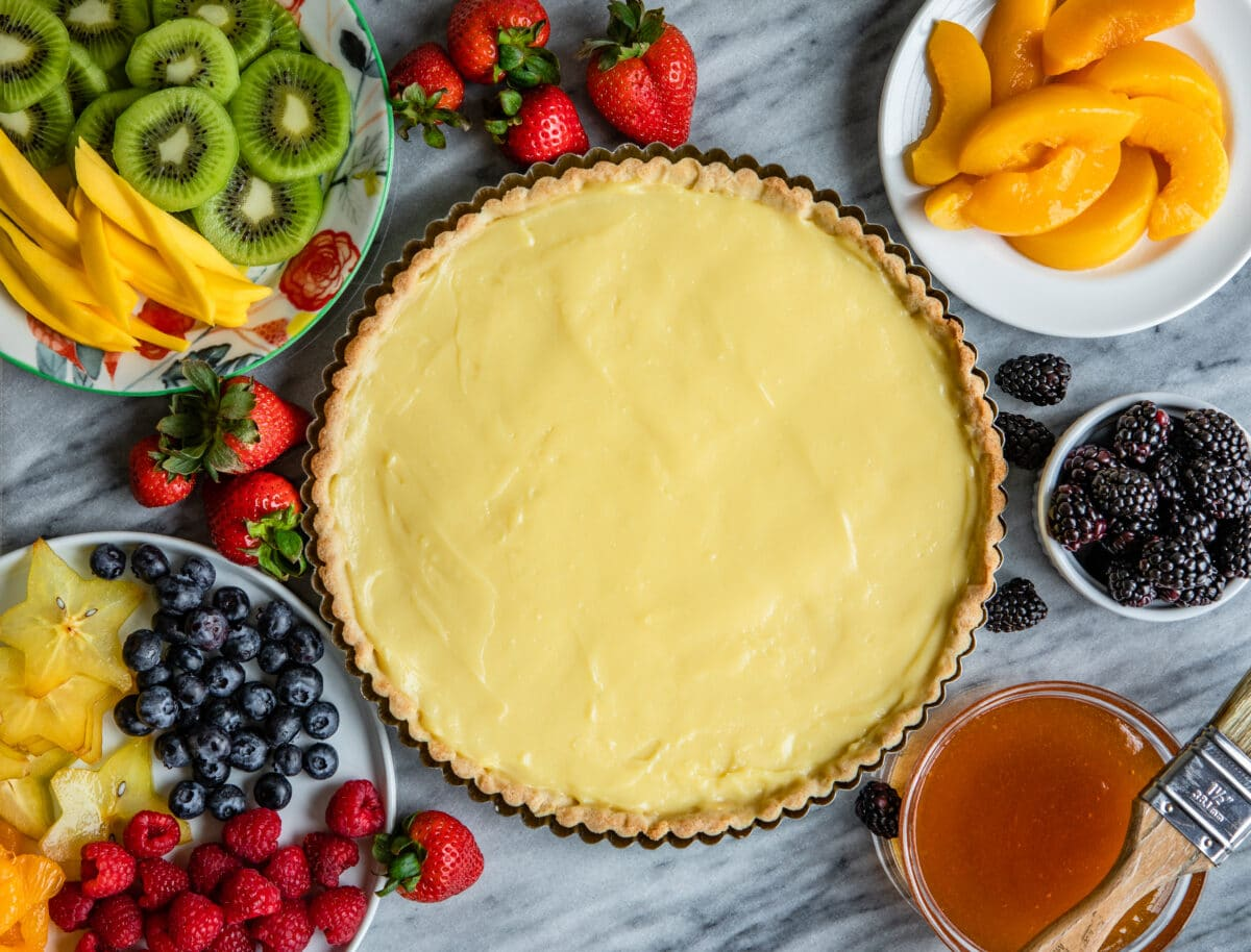 A tart crust with pastry cream inside and fresh fruit sitting around it.