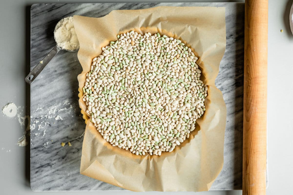 Tart dough crust with baking weights inside.