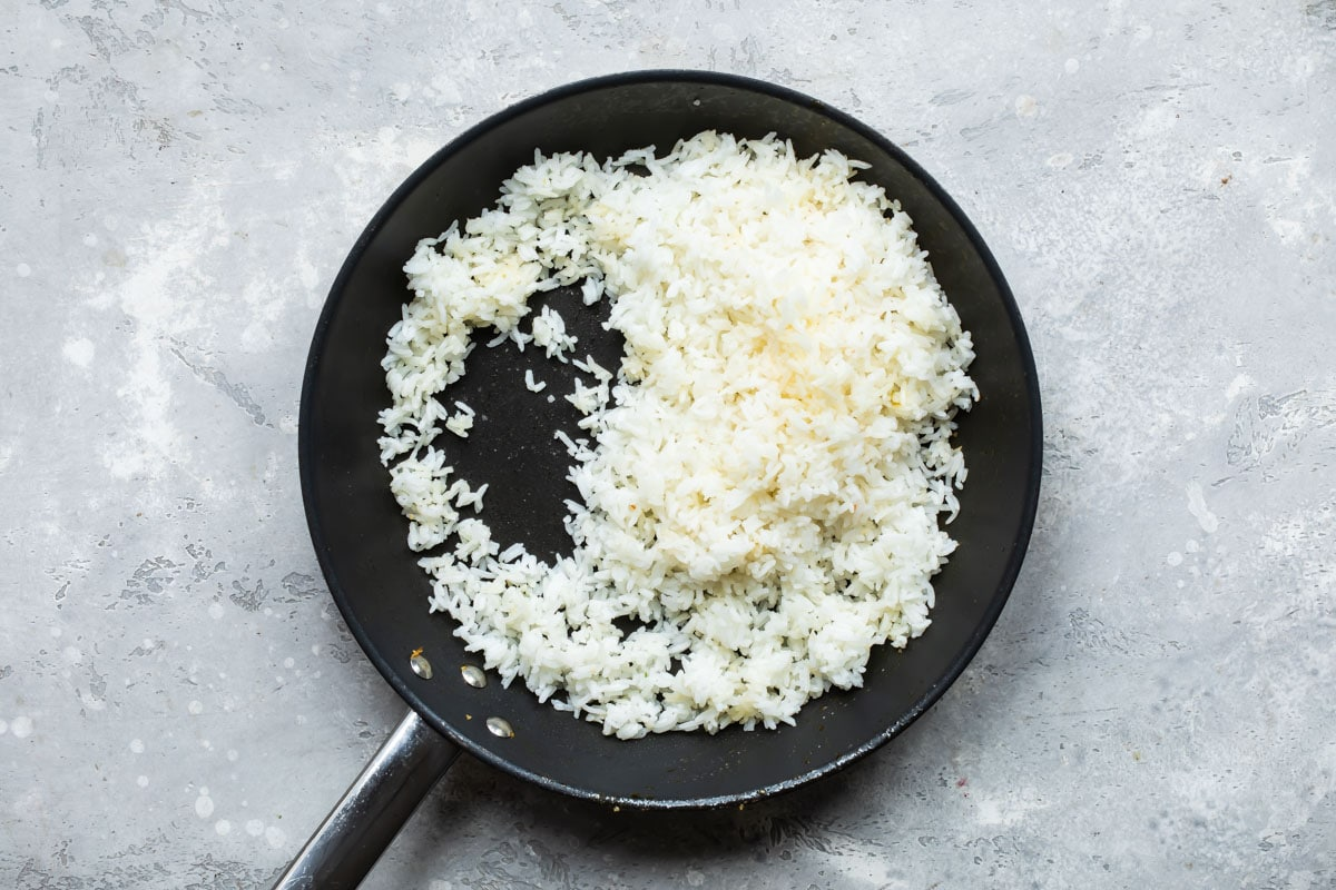 Cooked rice being fried in a skillet.