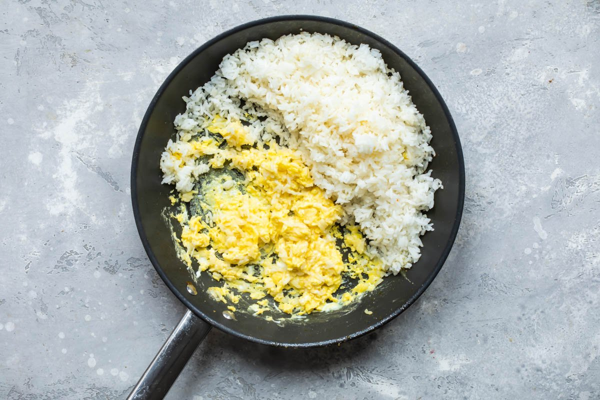 Cooked rice and eggs being cooked in a skillet.