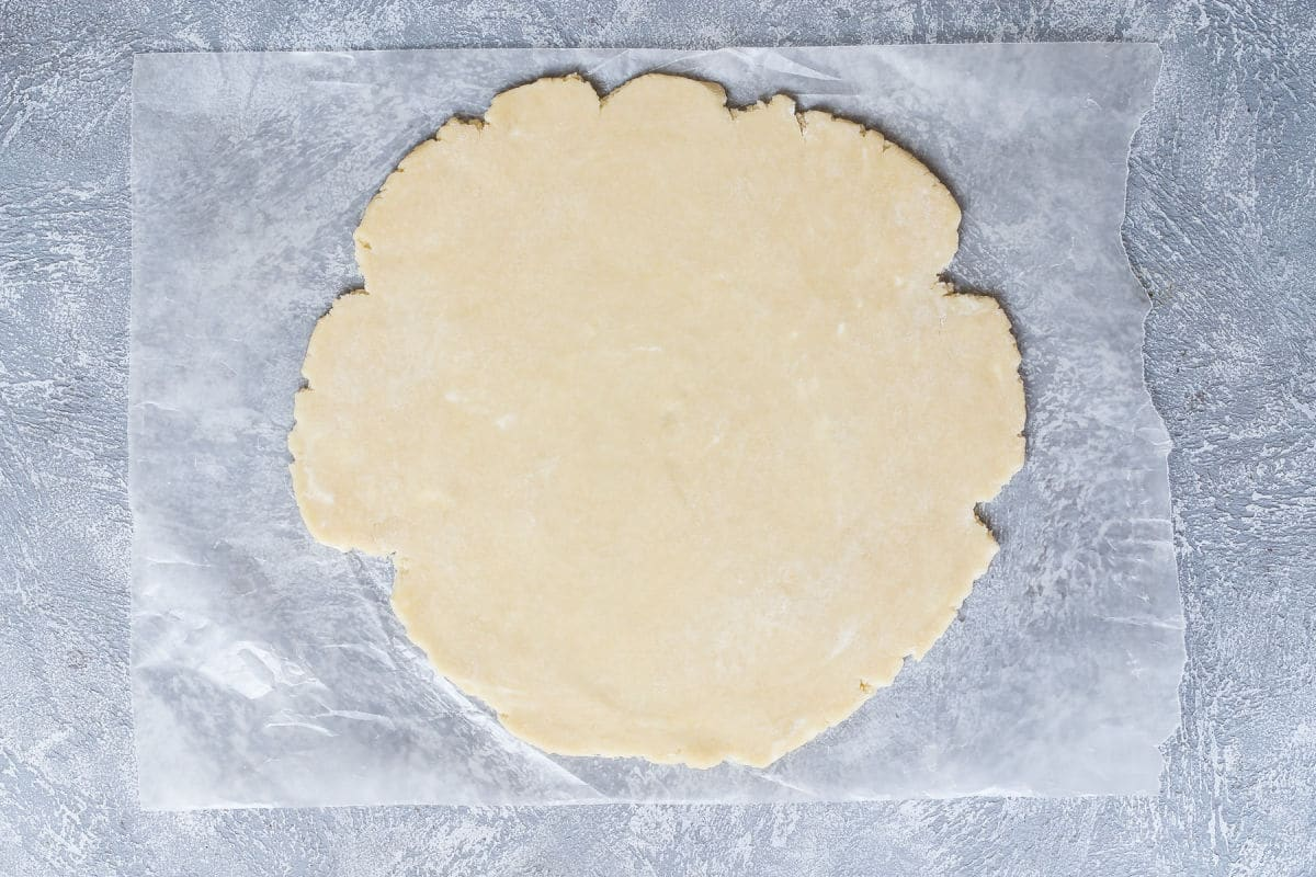 A pie crust rolled out on parchment paper.