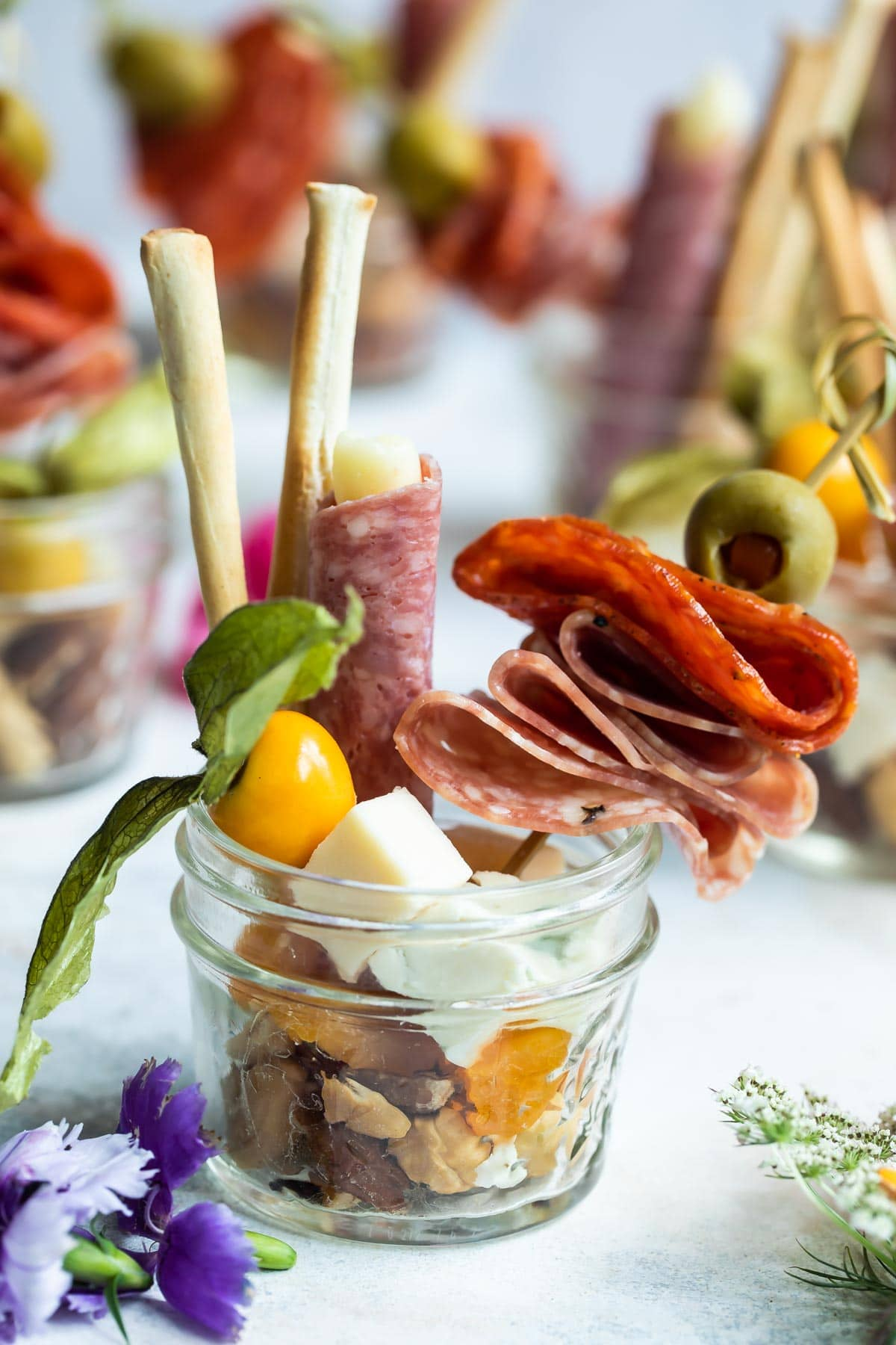 A mason jar filled with meats, olives, nuts, and breadsticks.