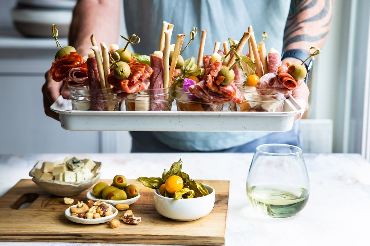 Someone holding a white tray filled with jarcuterie.