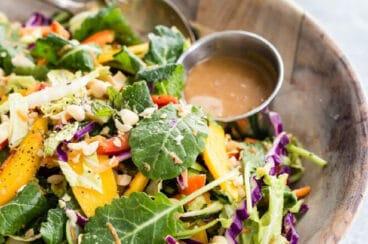A bowl of rainbow thai mango salad with peanut dressing on the side.