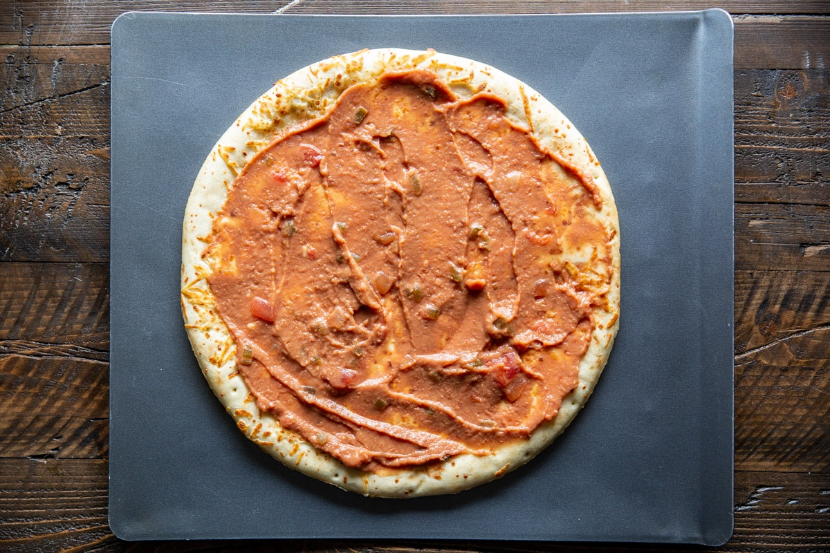Refried beans spread on a pizza crust.