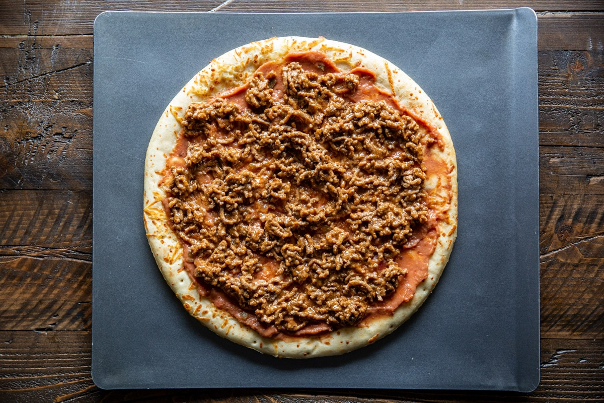 Refried beans and beef spread on a pizza crust.