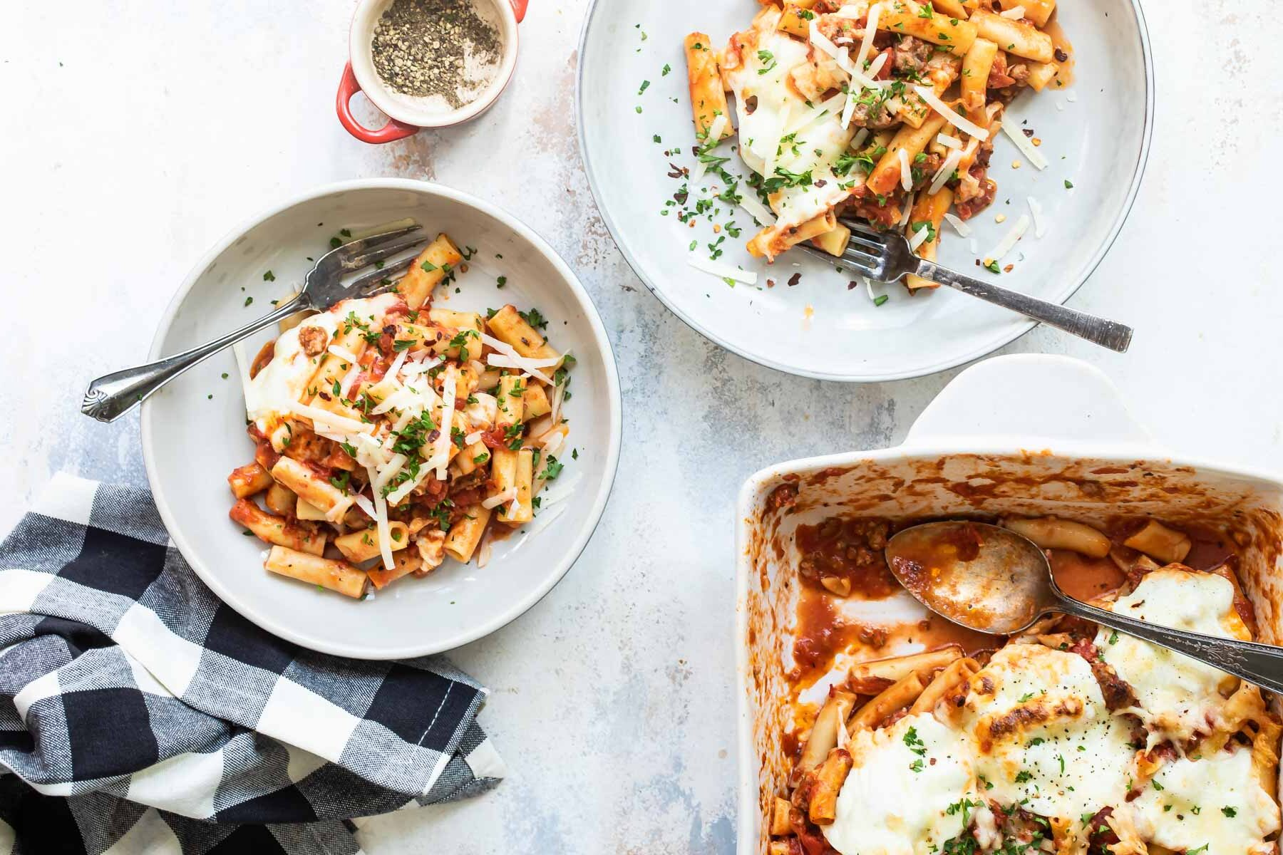 Two plates of baked ziti next to a pan of baked ziti.