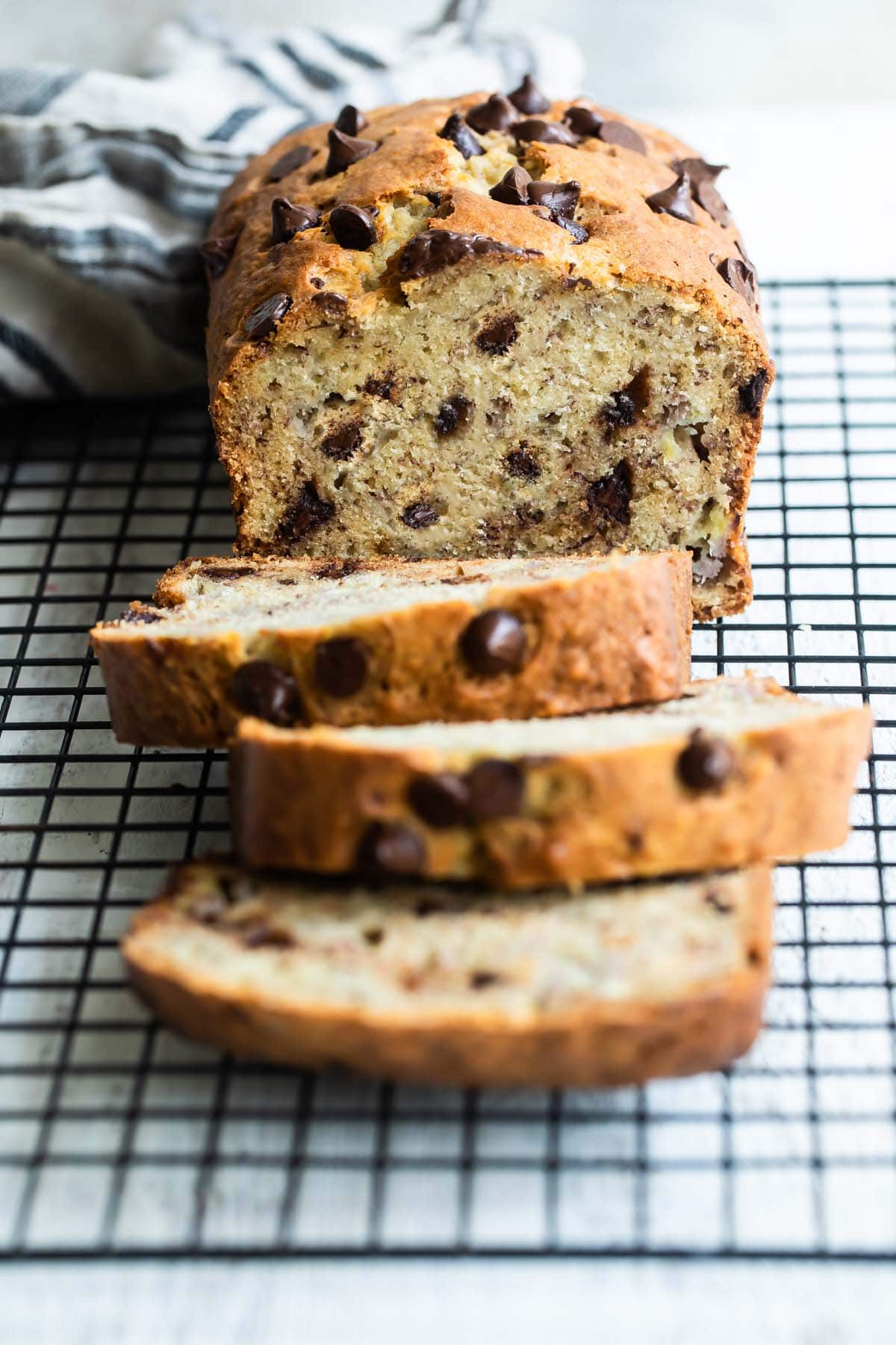 A sliced loaf of banana bread with chocolate chips.