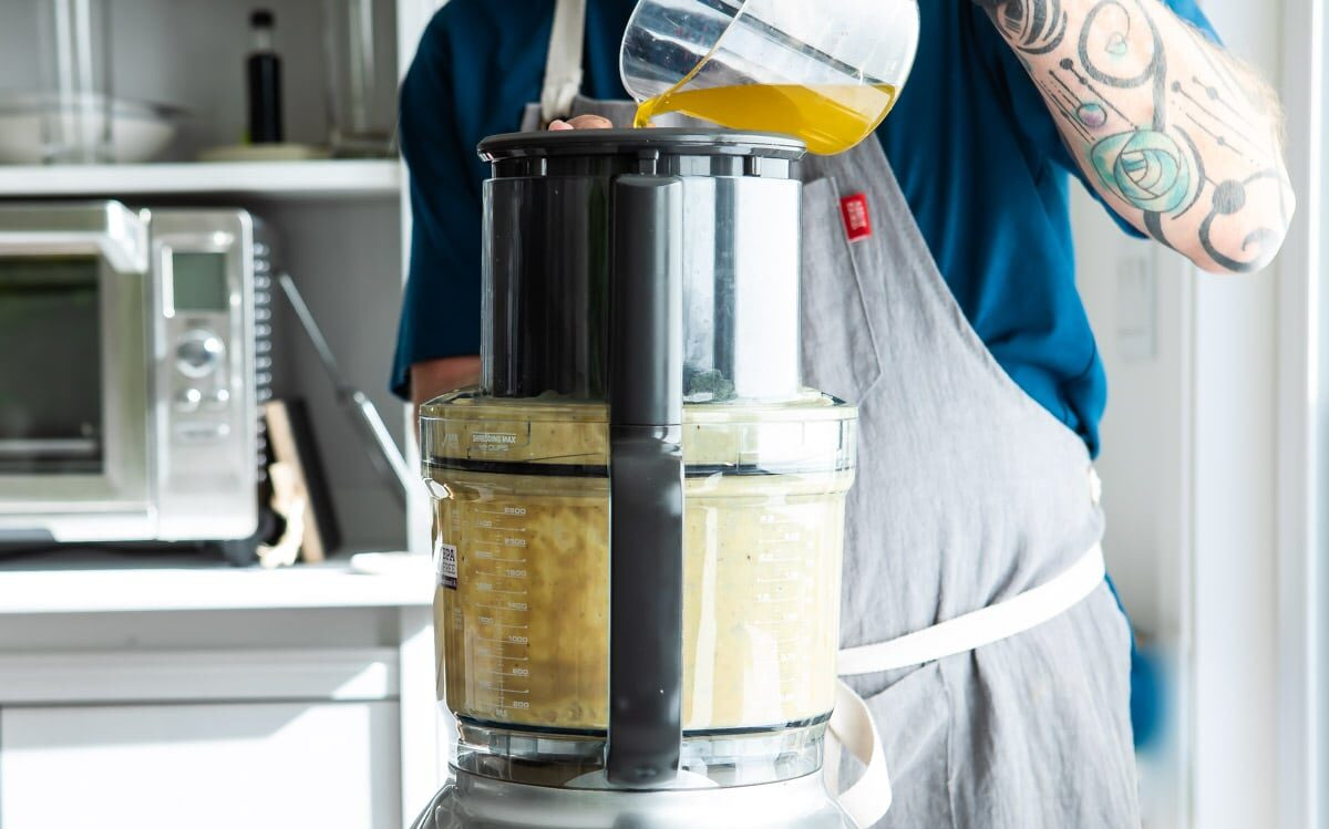 Oil being poured into a food processor.