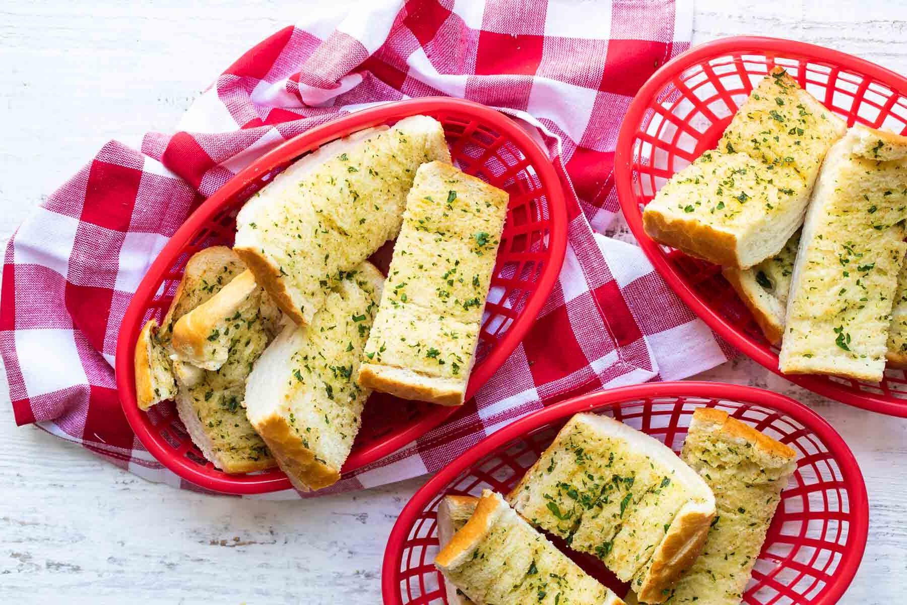 Garlic bread in three plastic red baskets.