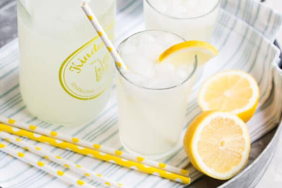 Lemonade in glasses on a silver platter with yellow and white straws and lemon garnish.