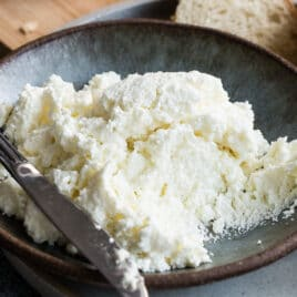 Homemade ricotta cheese in a blue bowl with a knife resting along the side.
