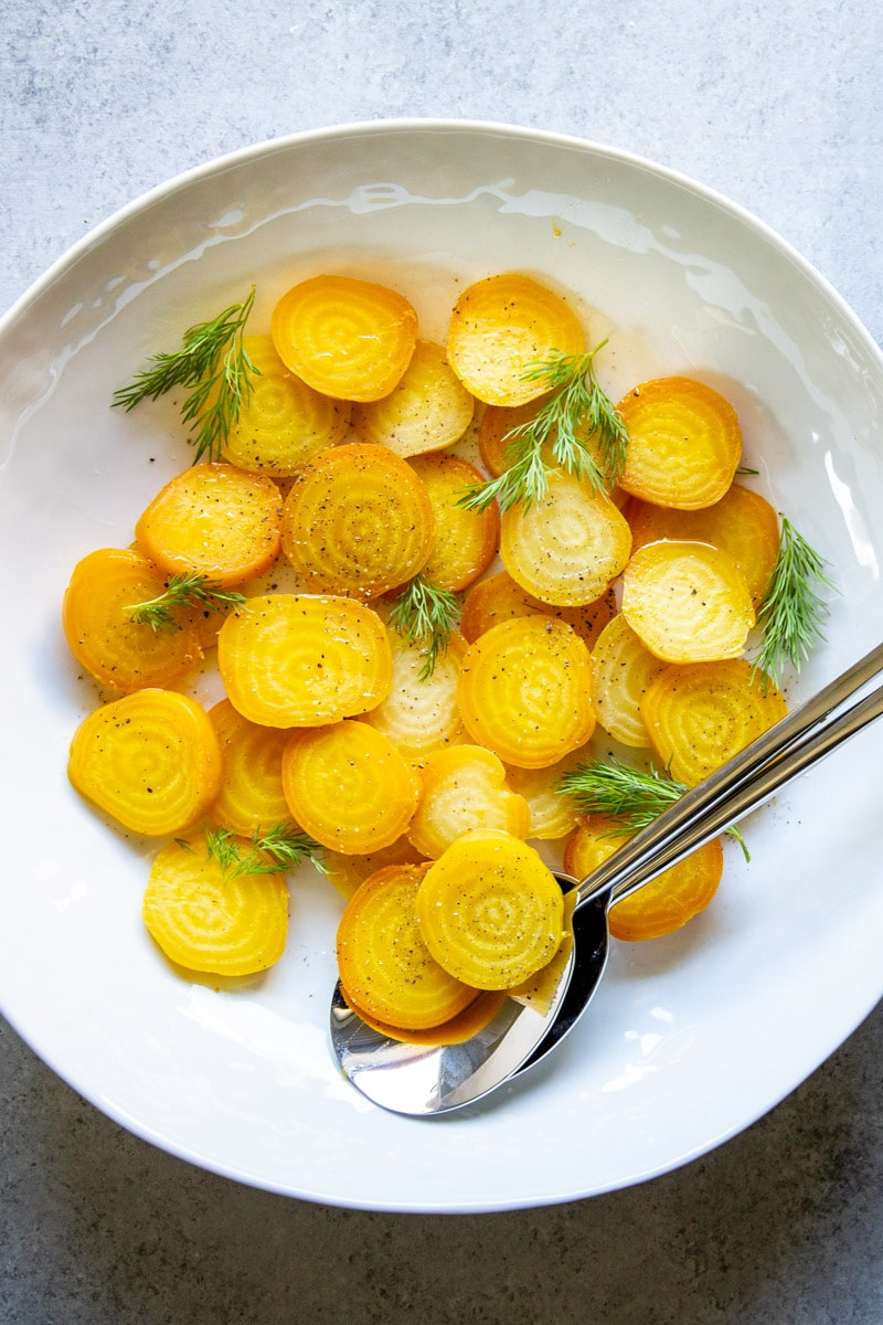 A platter of roasted golden beets, sliced and dressed with vinaigrette and fresh dill fronds.