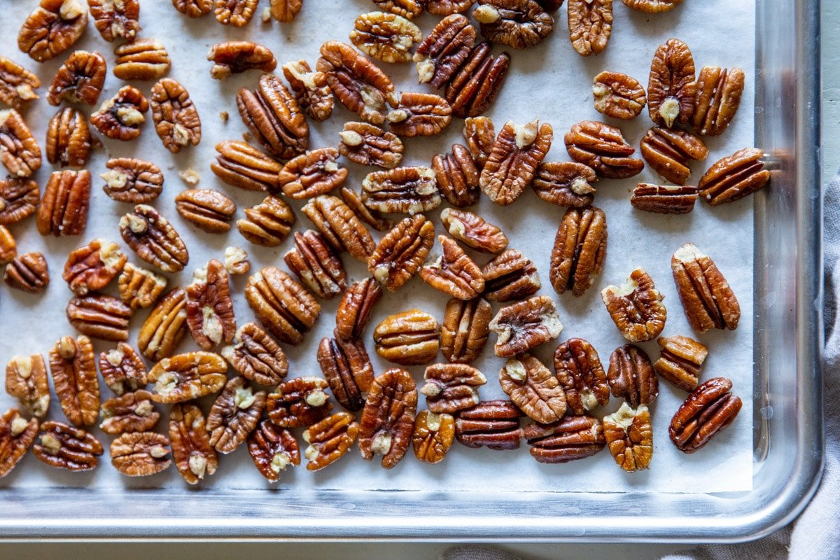 Toasted pecans on a baking sheet.
