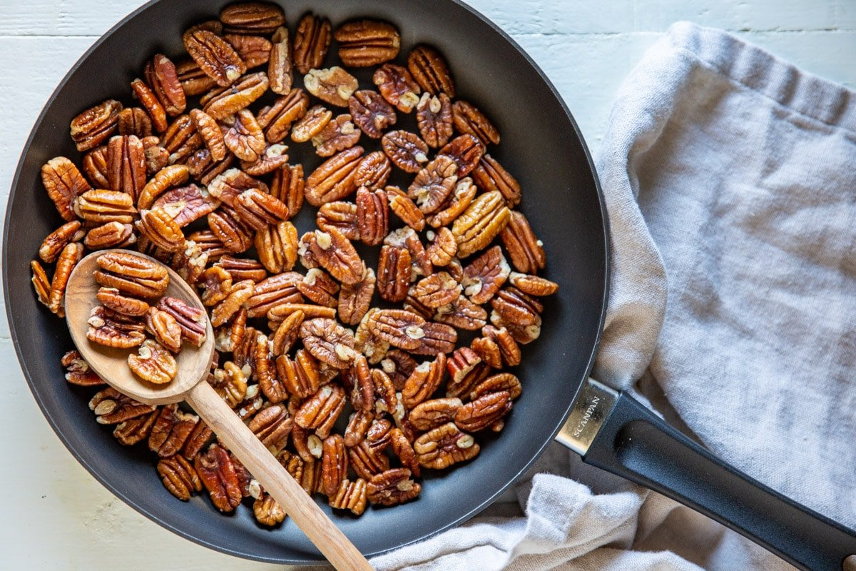 Toasted pecans in a skillet.