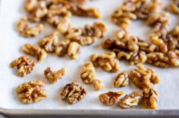 Toasted walnuts on a baking sheet.