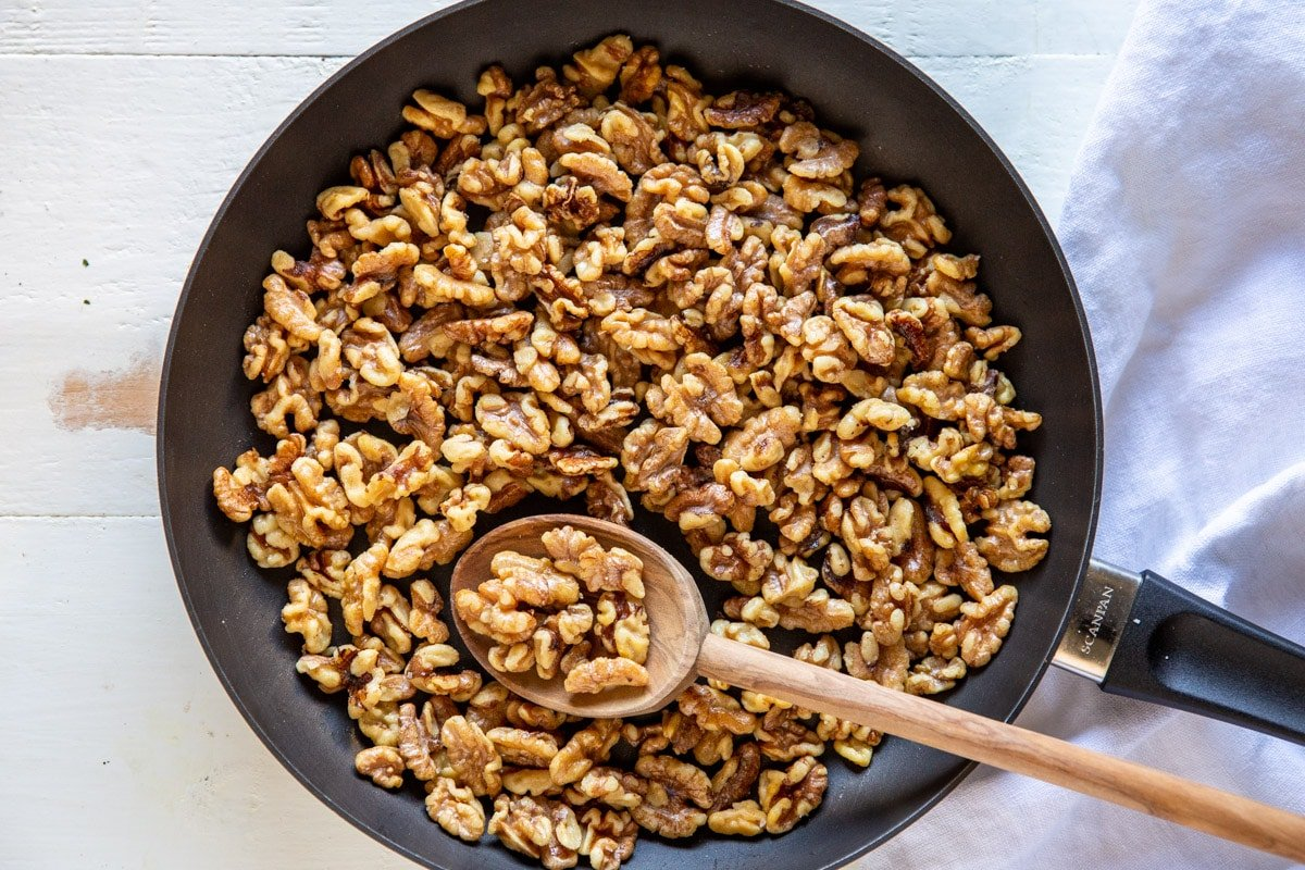 Toasted walnuts in a skillet.
