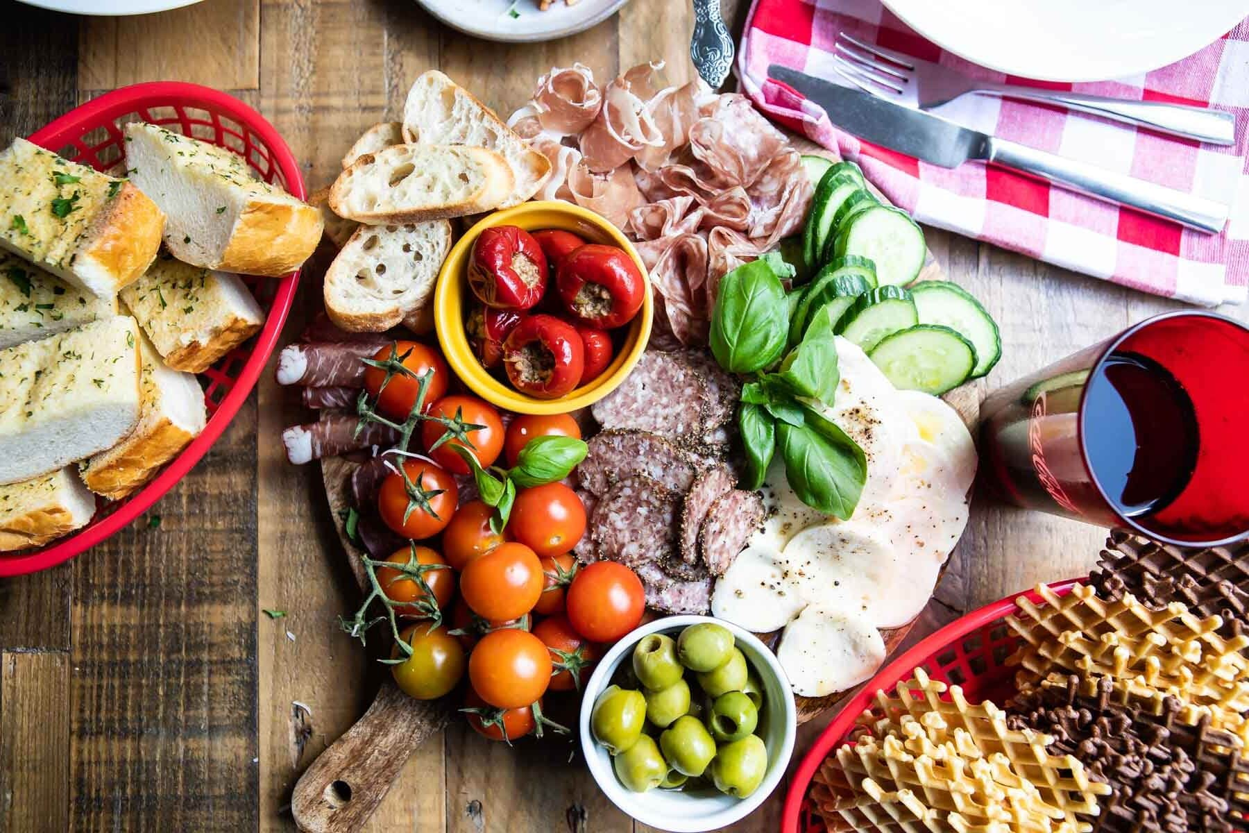 An antipasto platter on a wooden tray.